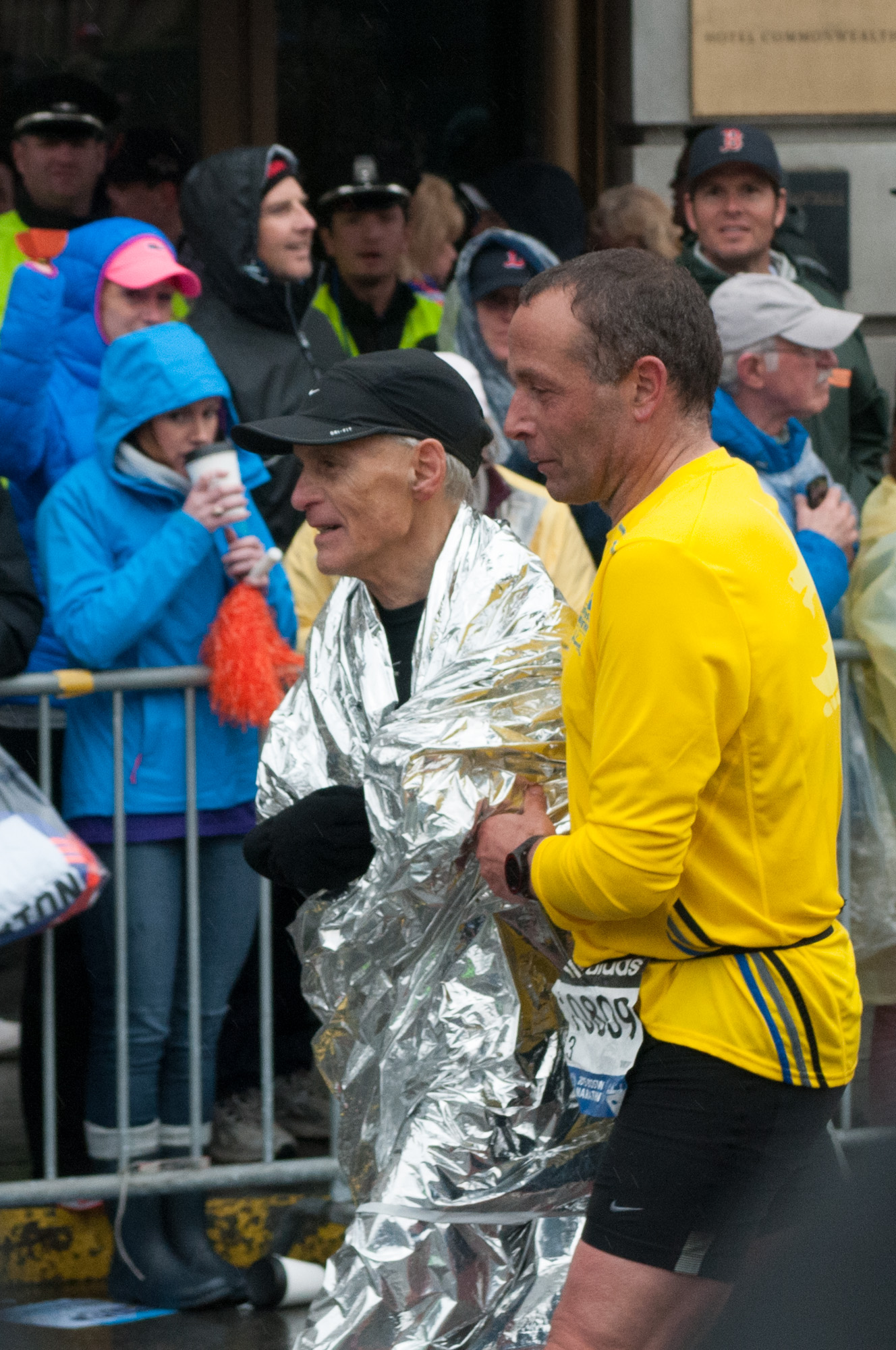 The runner in yellow was helping the runner in mylar finish